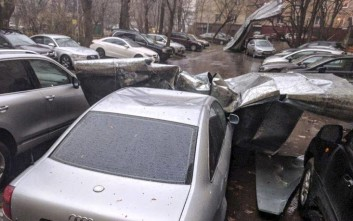 A piece of roof lays across a car after it fell during a heavy storm in Moscow, Russia, Saturday, April 21, 2018. (Kirill Snezhko, @argrento via AP)