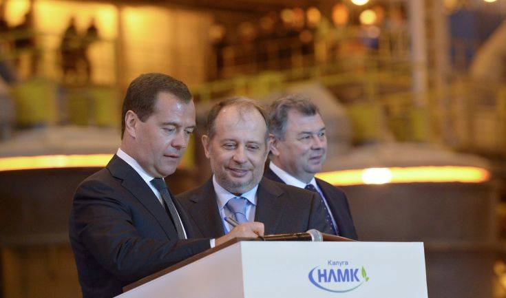 Russian Prime Minister Dmitry Medvedev, left, signs a book of guests at a newly opened metallurgical plant NLMK - Kaluga, at Maloyaroslavets,  about 150 km ( 93 miles) south-west of Moscow on Tuesday, July 23, 2013.  Kaluga region governor Anatoly Artamonov, right, and NLMK-Kaluga plant director Vladimir Lisin, center, look on. (AP Photo / RIA Novosti, Alexander Astafyev, Government Press Service)