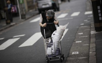 An elderly woman pushes a hand cart in Sugamo, Tokyo, Monday, June 10, 2013. Sugamo is a typical old shopping street with many stalls and shops which serves its neighbors, particularly old generation people,  for daily needs.  (AP Photo/Junji Kurokawa)