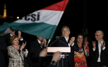 Hungarian Prime Minister Viktor Orban, center, flanked by his team, greets his supporters in Budapest, Hungary, Sunday, April 8, 2018. Preliminary results show populist Hungarian Prime Minister Viktor Orban has easily won a third consecutive term and his Fidesz party has regained its super majority in the parliamentary election. (AP Photo/Darko Vojinovic)