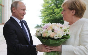 Russian President Vladimir Putin, left, greets German Chancellor Angela Merkel during their meeting at Putin's residence in the Russian Black Sea resort of Sochi, Russia, Friday, May 18, 2018. The meeting in Sochi is Merkel's first visit to Russia in a year and comes amid tense relations between Berlin and Moscow. (Mikhail Klimentyev, Sputnik, Kremlin Pool Photo via AP)