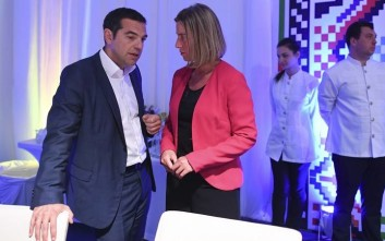 Greek Prime Minister Alexis Tsipras, left, speaks with European Union foreign policy chief Federica Mogherini during a dinner with EU and Western Balkan heads of state at the Sofia Tech Park in Sofia, Bulgaria, Wednesday, May 16, 2018. (Vassil Donev, Pool Photo via AP)