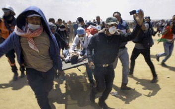 Palestinian medics and protesters evacuate a seriously wounded youth during a deadly protest at the Gaza Strip's border with Israel, east of Khan Younis, Gaza Strip, Monday, May 14, 2018. Thousands of Palestinians are protesting near Gaza's border with Israel, as Israel celebrates the inauguration of a new U.S. Embassy in contested Jerusalem. (AP Photo/Adel Hana)
