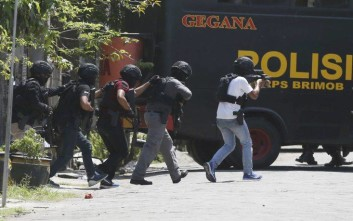 Police officers conduct a raid on the house of the family that carried out the bombing of Surabaya police headquarters, in Surabaya, Tuesday, May 15, 2018. The Indonesian family brought its 7-year-old daughter to the suicide bomb attack it launched Monday on the police headquarters in the country's second-largest city, authorities said, a day after members of another family conducted coordinated suicide bombings on three city churches that killed a number of people. (AP Photo/Achmad Ibrahim)