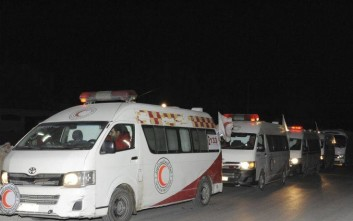 In this photo released by the Syrian official news agency SANA, ambulances of the Syrian Arab Red Crescent queuing during a human mission to evacuate sick and wounded people from the eastern Ghouta, near Damascus, Syria, Thursday, Dec. 28, 2017. The government recently tightened its siege of eastern Ghouta, home to some 400,000 people, leading to severe shortages of food, fuel and medicine as winter sets in. (SANA via AP)