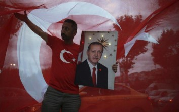 A man hold a picture of Turkey's President and ruling Justice and Development Party, or AKP, leader Recep Tayyip Erdogan while celebrating outside the party headquarters in Istanbul, Sunday, June 24, 2018. Early partial results in Turkey's presidential elections Sunday showed incumbent Recep Tayyip Erdogan in the lead, with challenger Muharrem Ince in second place. (AP Photo/Emrah Gurel)