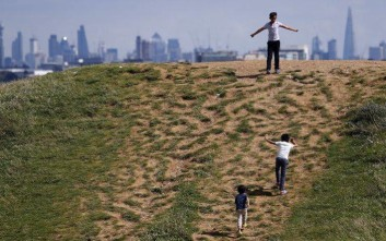 Children play on top of one of the Northala Fields hills in London, Thursday, Aug. 17, 2017. Four large earth mounds were built using waste from the original Wembley Stadium and the building of the White City Westfield shopping centre. The mounds reduce noise pollution, provide a view point and are an interesting landmark for the area in west London. In the background are, at left, the Post Office Tower and at right The Shard which was Europe's tallest building when it was built. (AP Photo/Frank Augstein)