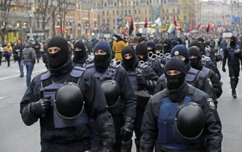 Ukrainian riot police walk in front of supporters of former Georgian President Mikheil Saakashvili during a protest march in Ukraine in Kiev, Ukraine, Sunday, Dec. 10, 2017. From his jail cell in Ukraine's capital, opposition leader Mikheil Saakashvili is calling on supporters to rally for the impeachment of the president. (AP Photo/Sergei Grits)