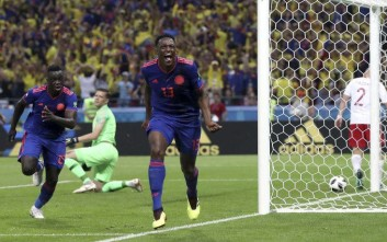 Colombia's scorer Yerry Mina, center, and his teammate Davinson Sanchez, left, celebrate the opening goal during the group H match between Poland and Colombia at the 2018 soccer World Cup at the Kazan Arena in Kazan, Russia, Sunday, June 24, 2018. (AP Photo/Thanassis Stavrakis)
