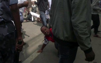 In this image made from video, people fall over in the rush to get away, after an explosion at a rally for Ethiopia's new Prime Minister, in Addis Ababa, Saturday, June 23, 2018. A witness near the scene of a deadly blast at a huge rally for Ethiopia's new prime minister says the man who tried to throw the grenade was wearing a police uniform. Abraham Tilahun tells The Associated Press that other police officers restrained the man from throwing the grenade as Prime Minister Abiy Ahmed was waving to the crowd of tens of thousands. (AP Photo)