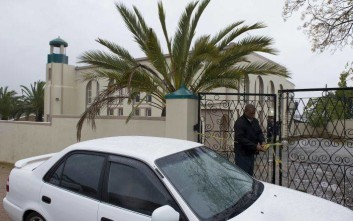 An investigator attends to the gates of a mosque in Malmesbury, near Cape Town, South Africa Thursday June 14 2018.  South African police say a man with a knife fatally stabbed two people and wounded several others at a mosque near Cape Town before police shot and killed the attacker. (AP Photo Nasief Manie)