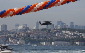 A military helicopter flies over the Bosporus Strait separating Asia and Europe, background, following an election rally of Turkey's President and ruling Justice and Development Party leader Recep Tayyip Erdogan in Istanbul, Friday, June 22, 2018. Turkey holds parliamentary and presidential elections on June 24, 2018, deemed important as it will transform Turkey's governing system to an executive presidency.(AP Photo/Lefteris Pitarakis)