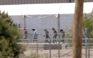 Detainees are seen outside tent shelters used to hold separated family members, Friday, June 22, in Fabens, Texas.  The U.N human rights office says President Donald Trump's decision to stop the U.S. policy separating migrant parents from their children doesn't go far enough. (AP Photo/Matt York)