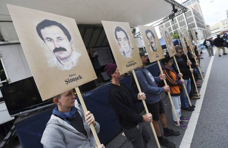 Demonstrators hold signs with people killed by the NSU outside the court in Munich, southern Germany, prior to the verdict Wednesday, July 11, 2018. (Tobias Hase/dpa via AP)