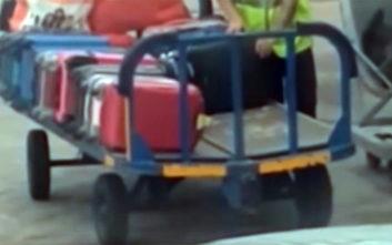 Υπάλληλος αεροδρομίου βάζει χέρι σε βαλίτσα επιβάτη