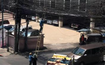 Εργάτες προσπαθούσαν με μία σκάλα από μπαμπού να ξεμπερδέψουν καλώδια εν μέσω κίνησης