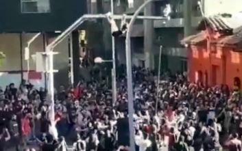 Χιλή: Κοπέλα ανεβαίνει σε στύλο, αχρηστεύει κάμερα ασφαλείας και πέφτει στην αγκαλιά διαδηλωτών