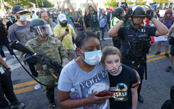 Η φρίκη στις ΗΠΑ μέσα από ένα φωτογραφικό κλικ: Αστυνομικός σημαδεύει εξ' επαφής κοριτσάκι στους ώμους του πατέρα του